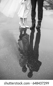Feet of the bride and groom on the wet road, walk under the rain, the bride and groom walk in rainy weather, couple reflected in puddles on the road,  wedding in rainy and windy weather