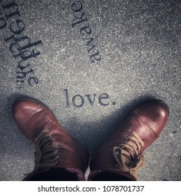 Feet in brown leather boots and black legging over the word LOVE on concrete floor. Vignetted and crossed processed.