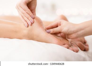 Feet care. Woman receiving foot and finger massage, closeup