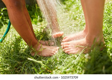 Feet of children are wet splashed to cool off in the summer in the garden
