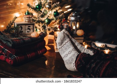 Feet in Christmas socks. Close up on feet. Winter and Christmas holidays concept. The cup of hot drink. Background with christmas decor. Scandinavian hygge styled Christmas composition. Cozy winter.