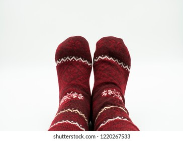 Feet with christmas socks on white background