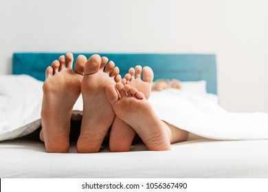 Feet close up of young loving couple enjoying on the bed