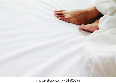 Feet in comfortable bed. Close up of feet in a bed under white blanket. Bare feet of a woman peeking out from under the cover.Top view with copy space (selective focus).