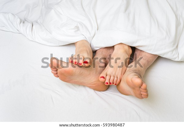 Feet of a couple in bed under the white blanket