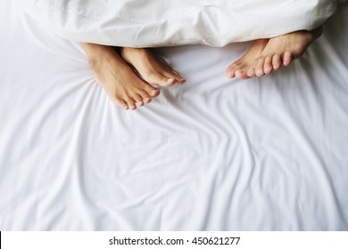 Feet of couple in comfortable bed. Close up of feet in a bed under white blanket. Bare feet of a man and a woman peeking out from under the cover.Top view with copy space (selective focus).