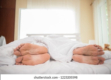 Feet of couple facing away from each other.