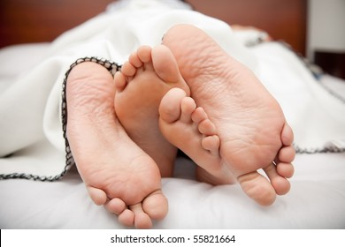 Feet of a couple lying in bed