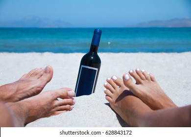 Feet of the couple on the beach with bottle of wine. Summer.