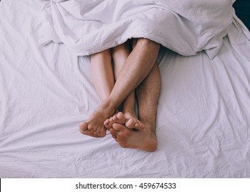 Feet of couple side by side in bed