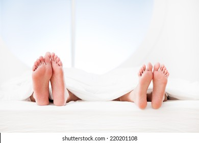 Feet of a couple sleeping side by side.