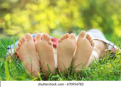 Feet of cute little children lying on green grass in park