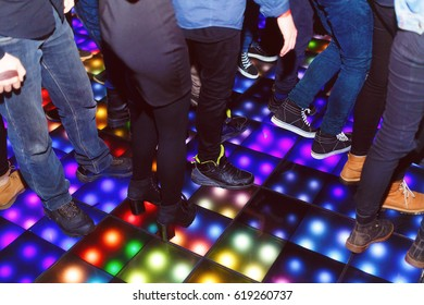 The feet of the dancers on the LED dance floor