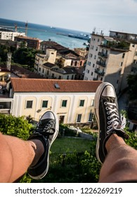 Feet dangling from Italian roof top with italian architektur and a view onto the city skyline and ocean