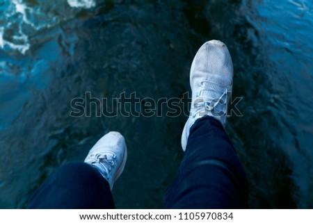 Feet dangling over water
