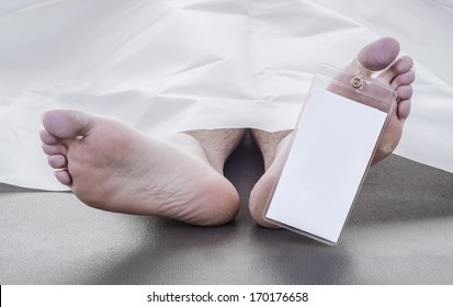 feet of a deceased man under white blanket with a blank toe tag