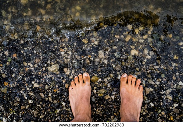 Feet at the edge of the water