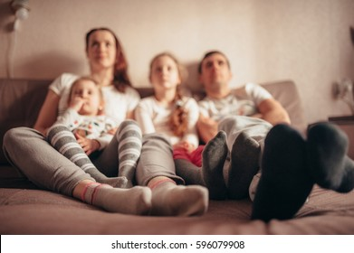 Feet of a family sitting on the couch. in focus