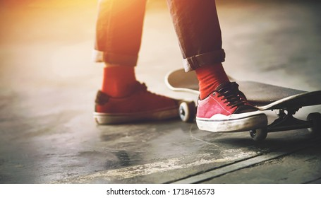 The feet of a fashionable teenager in jeans, red socks, and pink sport sneakers, and next to a gray skate, brightly lit by the light of the sun.