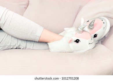 feet female wearing unicorn trendy slippers laying on counch, soft pastel colours beige and pink