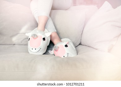 feet female wearing unicorn trendy slippers sitting on counch, soft pastel colours beige and pink