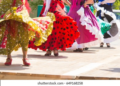 Feet of flamenco dancers, performing on a wooden stage in summer city festival