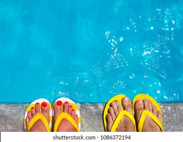 Feet in flip flops on stone background on poolside. Summer family vacation concept