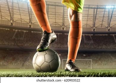 feet of football player on soccer ball for kick-off