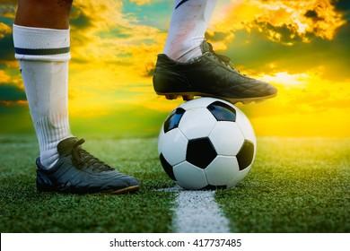 feet of football player tread on soccer ball for kick-off