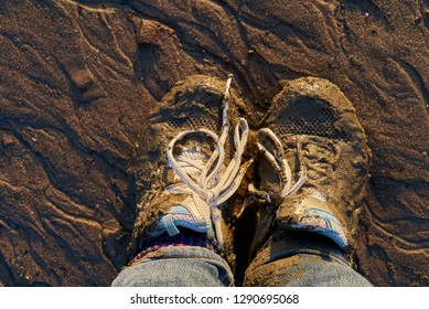 feet with former white sports shoes that have been stuck in the mud