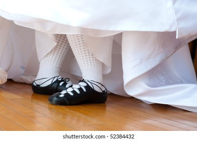 Feet in ghillies surrounded by wedding dress