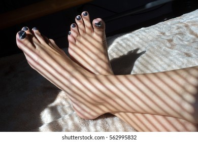 the feet of the girl. Light through window blinds