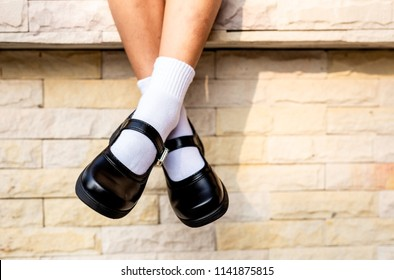 Feet of girl wear a black student shoes with wall background