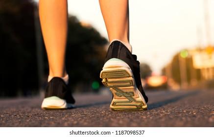 feet of girls running along the street close-up on a city street
