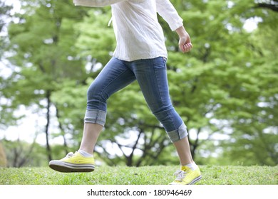 Feet of Japanese student walking through the green nature,