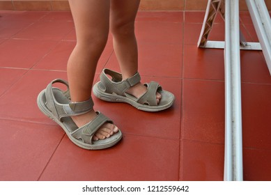 feet of the kid in his mother's sandals, which are bigger for him, shot close-ups next to some kind of stand