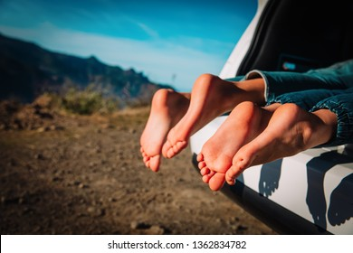 feet of kids relax while travel by car in mountains