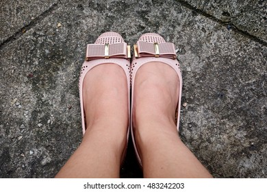 Feet in leather flat shoes on pavement background, top view