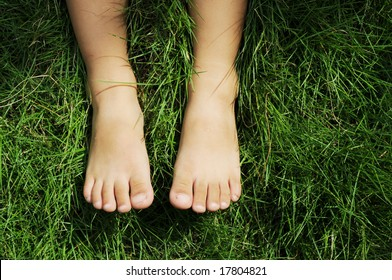 The feet of a little boy on the meadow