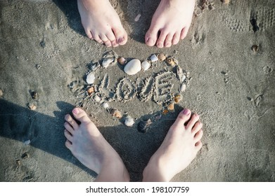 Feet of loving couple and a heart made ??of seashells on the sand on the beach