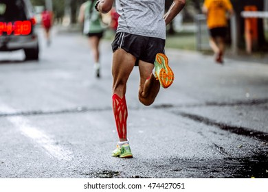 feet male athlete taping on calf muscles, running city marathon