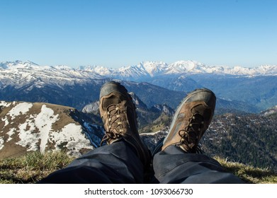 The feet of a man in boots against the background of snow-capped mountains after climbing to the top on a sunny spring morning