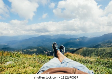 The feet of a man in boots against the background of  mountains after climbing to the top on a sunny spring morning