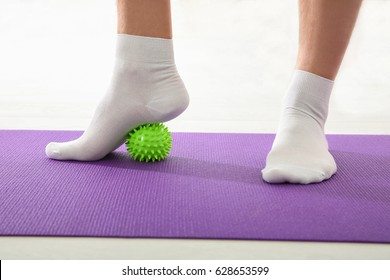 Feet of man doing exercises with stress ball in clinic