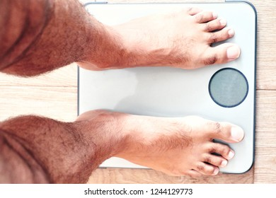 Feet man on top of an empty weight scale