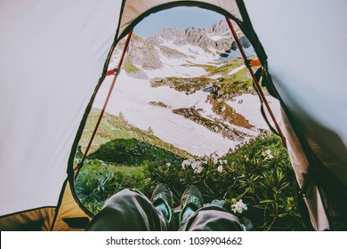 Feet Man relaxing with mountains view from tent camping entrance outdoor Travel wanderlust Lifestyle concept adventure vacations outdoor