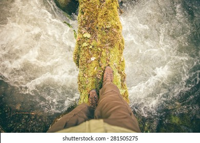 Feet Man trekking boots hiking outdoor with river and stones on background Lifestyle Travel survival concept top view