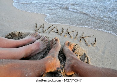 Feet of a man and a woman on the sand with Waikiki written on the sand, Fringe of Waikiki beach, footprint on the sand in Waikiki beach.