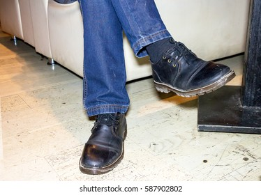 Feet men in jeans and black boots. A man sits on a white sofa