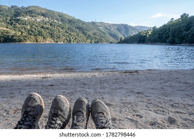 Feet with mountain boots point of view. Couple on a date in a beach in Ponte Nova, Cabril, Geres National Park